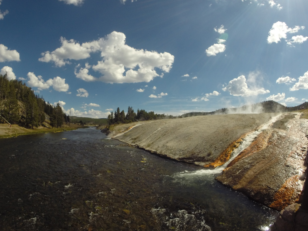 Hot water from the Grand Prismatic Spring runs into the river
